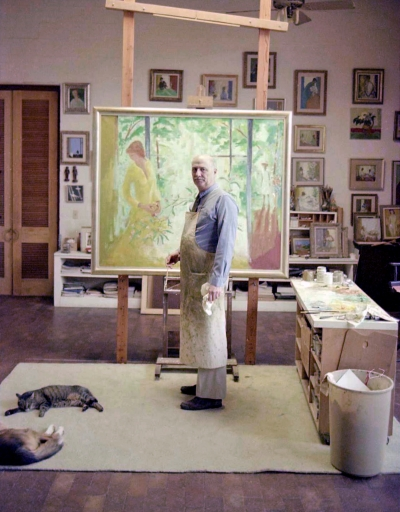Artist painting in his studio with cat and dog